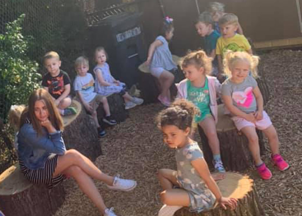 Childcare students sitting outside on logs