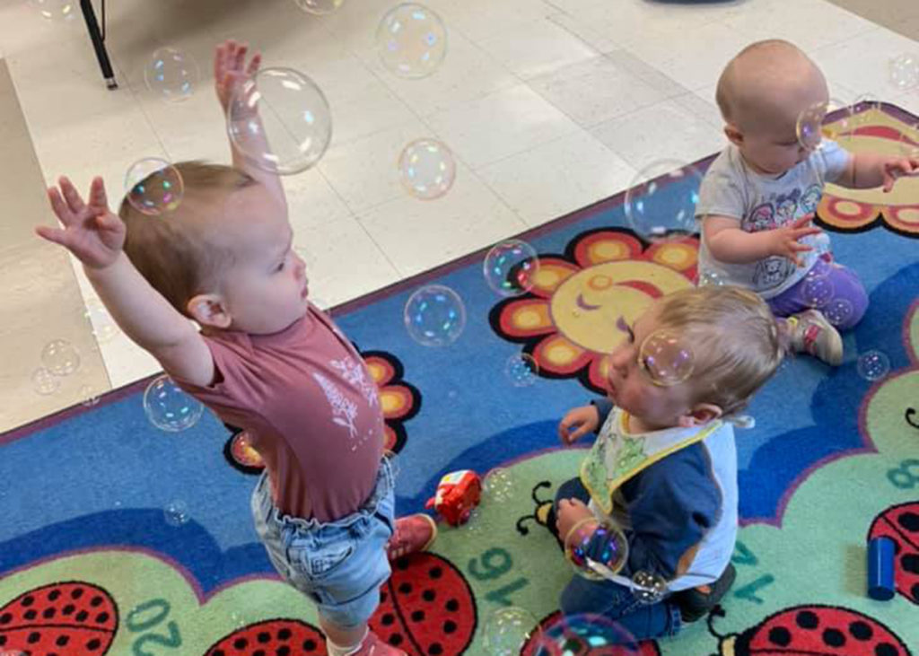 Childcare toddlers playing with bubbles